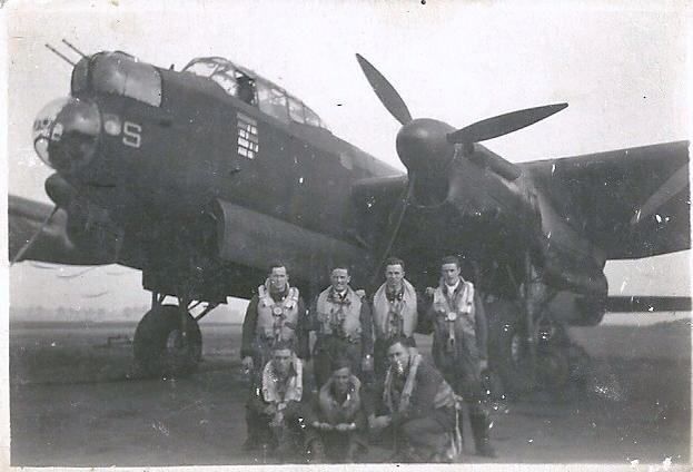 Crew of bomber sitting outside plane